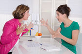 Two business woman disputing in the office having disagreement. — Stock Photo
