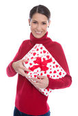 Isolated smiling young woman in red holding a present in her han — Stock Photo