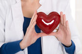 Female doctor holding a red heart in her hands - for concepts. — Stock Photo