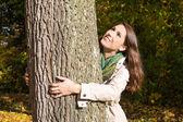 幸福的年轻女人,在秋天尴尬一棵树. — 图库照片