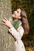 Gelukkig jonge vrouw in herfst embrassing een boom. — Stockfoto