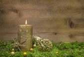 First advent: golden candle burning before wooden background. — Stok fotoğraf