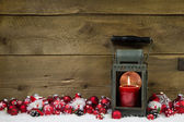 Wooden christmas background with red candle in a latern and snow — Stok fotoğraf