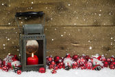 Christmas latern with red candle and balls on wooden background. — Zdjęcie stockowe