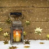 Christmas mood: old rustic latern on a snowy background. — Stock Photo