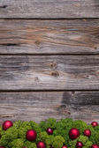 Old background of wood with red xmas balls and moss. — Stok fotoğraf