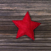 Red christmas star of felt on wooden background for decoration. — Stock Photo