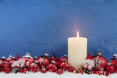 Blue wooden christmas background with a white candle and red bal — Stock Photo
