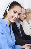 Smiling woman on the phone in a call center wearing blue blouse. — Foto Stock