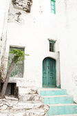Old house facade with green wooden door looking like a ruin. — Stock Photo