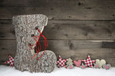 Wooden christmas background in red and grey with santa boot. — Stockfoto