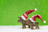 Two wooden reindeer: funny green and white christmas background. — Stock Photo