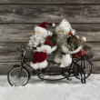 Two funny santa claus on a tandem in hurry for christmas shoppin — Stock Photo #50140569