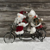 Two funny santa claus on a tandem in hurry for christmas shoppin — Stock Photo