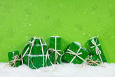 Green christmas gift boxes on white snowy background. — Stock Photo