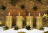 Four golden burning candles for advent on wooden rustic backgrou — Foto de Stock