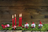 Four red burning christmas candles on wooden background with gre — Stock Photo