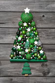 Green christmas decoration with wood: tree of balls on grey back — Stock Photo