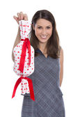 Isolated smiling pretty woman holding a gift with red hearts in  — Stock Photo