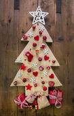Decoration: handmade carved christmas tree with red miniatures. — Stock Photo