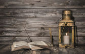 Old vintage background with book and feather and a rustic lanter — Stock Photo