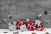 Christmas presents in red and silver on wooden grey background. — Stock Photo