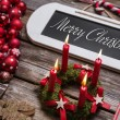 Merry christmas greeting card with four red candles and text. — Stock Photo #50775147