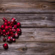 Christmas decoration: red balls on old wooden rustic background. — Stock Photo #50775611