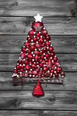 Red christmas tree with balls on old wooden shabby background. — Stock Photo