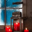 Christmas atmosphere: four red burning candles in the window. — Stock Photo #50917445