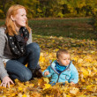Indian summer: Young woman with her baby in autumn. Family conce — Stock Photo