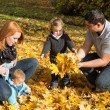 Happy young family in autumn making a walk and play with maple l — Stock Photo #50928987