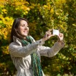 Young woman making a photo with her phone in autumn. — Stock Photo #50932057
