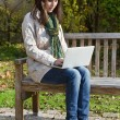 Young woman in autumn sitting on a park bench writing something — Stock Photo #50932361