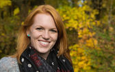 Natural red-haired young smiling woman in autumn on a walk. — Foto de Stock