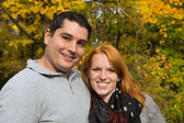 Happy young couple in autumn making a walk on the fresh air. — Stockfoto
