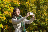 Young woman making a photo with her phone in autumn. — Stock Photo