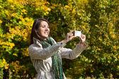 Młoda kobieta, co zdjęcie z jej telefon w jesieni. — Zdjęcie stockowe