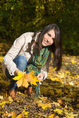 Happy young woman on a walk in autumn holding leaves in her hand — Stock Photo