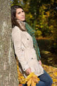 Dreaming young woman leaning on a tree trunk in fall. — Stock Photo