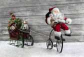 Funny christmas greeting card with Santa on a bike pulling a sli — Zdjęcie stockowe