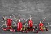 Four red burning wax advent candles on wooden natural grey backg — Stockfoto
