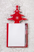 Christmas wishlist: white and red writing pad with a tree. — Stock Photo