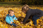 Autumn item: brother and sister having fun in autumn playing wit — Zdjęcie stockowe
