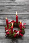 Greeting card: Four red burning advent candles on wooden grey ba — Zdjęcie stockowe
