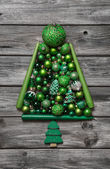 Green christmas tree of balls decorated on wooden background. — Stockfoto