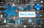 Merry christmas greeting card in blue and white with a wooden si — Stock Photo