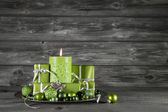 Green christmas decoration with candle and presents on wooden gr — Stockfoto