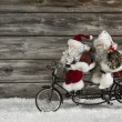 Funny wooden christmas background with two santa claus on a bicy — Stock Photo #50997515
