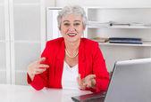 Attractive older smiling senior businesswoman sitting at desk we — Stock Photo